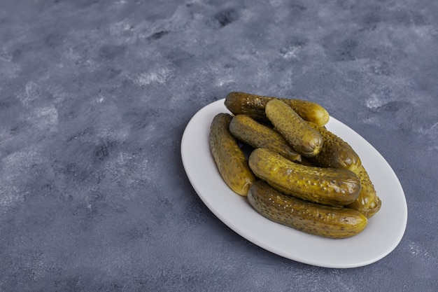 Pickled cucumbers on white plate on blue background.