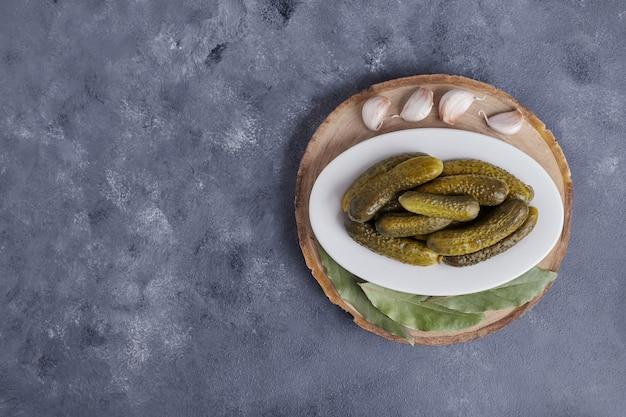 Cetrioli sottaceto sulla piastra bianca con aglio su sfondo blu.