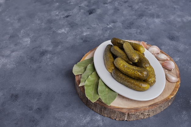 Pickled cucumbers on white plate with garlic on blue background.
