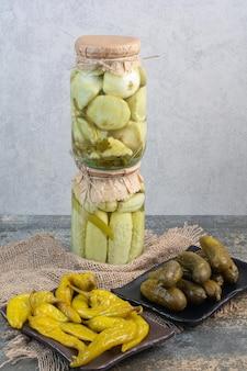 Cetrioli sottaceto con peperoni salati su tela di sacco. foto di alta qualità