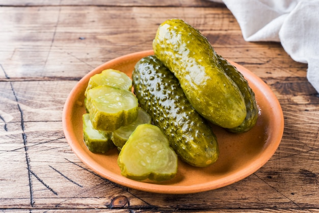 Pickled cucumbers in a wooden bowl dark rustic background