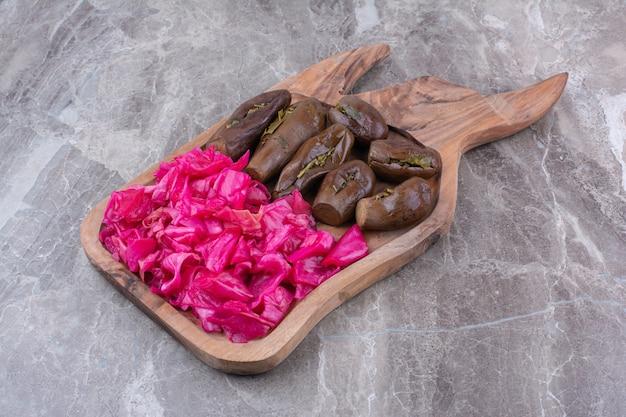 Маринованные баклажаны и краснокочанная капуста на деревянной доске.
