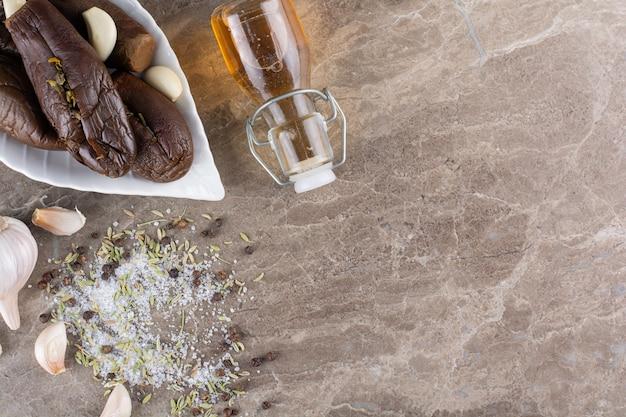신선한 마늘로 절인 가지를 돌 테이블에 놓습니다.