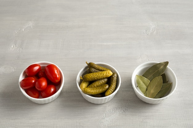 Pickled, fermented tomatoes and cucumbers and bay leaves in white bowls top view on a light wooden background with place for text.