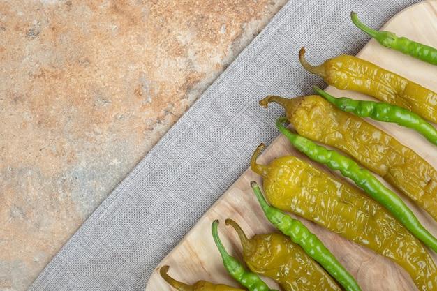 Peperoni verdi marinati e freschi sulla tavola di legno