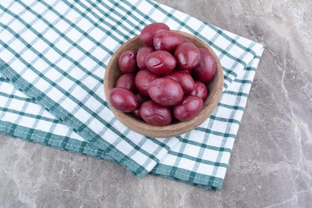 テーブルクロスと木製のボウルに漬けた果物。
