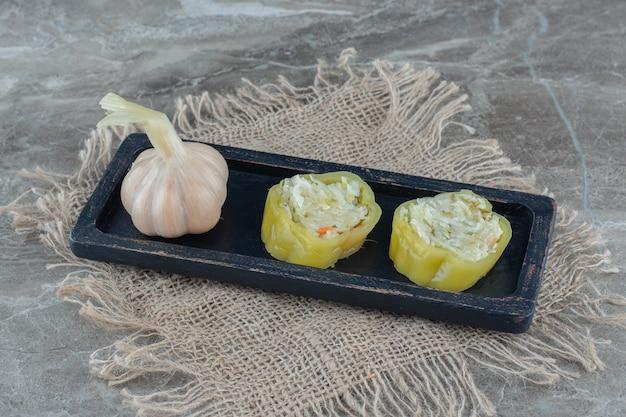 Маринованный чеснок и перец с начинкой на черной деревянной тарелке.