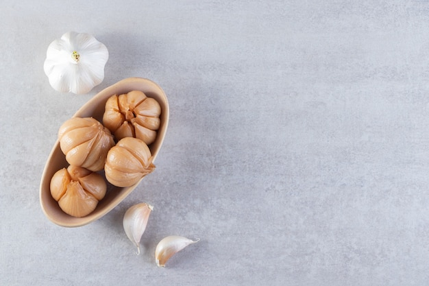 Pickled garlic placed on a stone background.