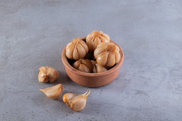 Pickled garlic placed on a stone surface.