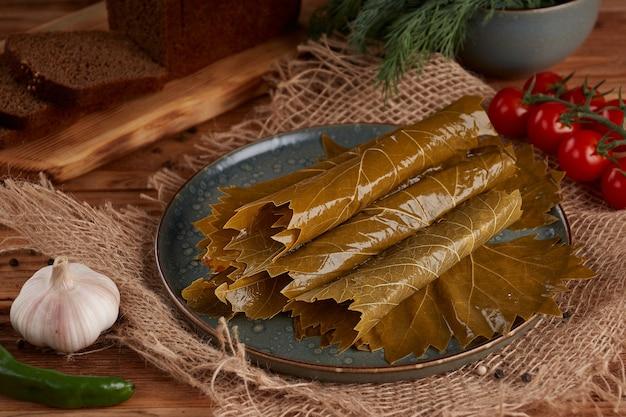木製の皿にぶどうの葉のピクルス