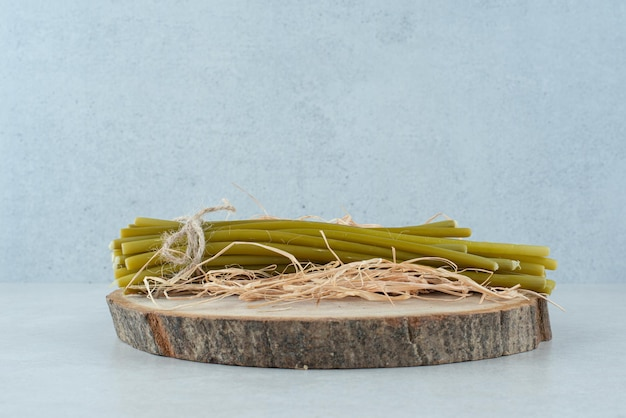 Pickled green beans on wood piece.