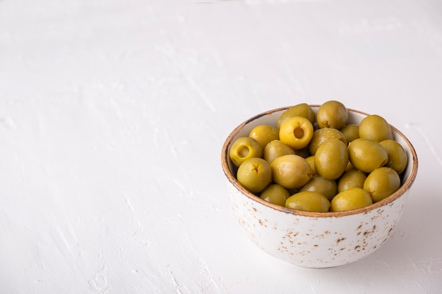 Pickled green olives in a bowl on white