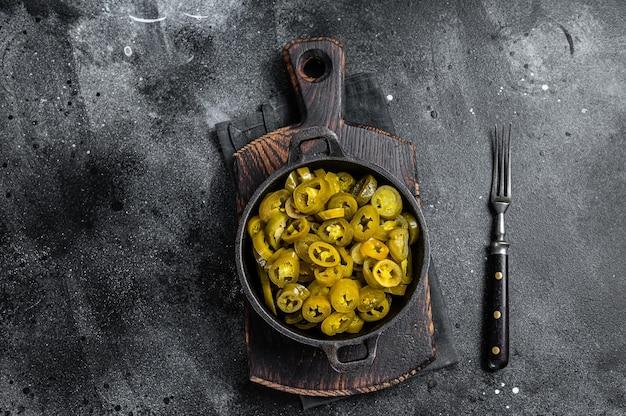 鍋にグリーンスライスハラペーニョのピクルス。黒の背景。上面図。