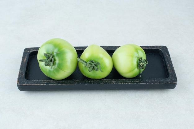 Маринованные зеленые помидоры на черной тарелке.