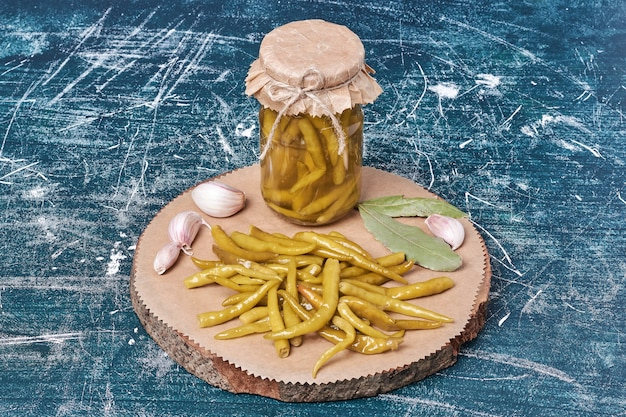 ガラスの瓶に入れ、葉とニンニクを添えた皿に唐辛子を漬け込んだ。