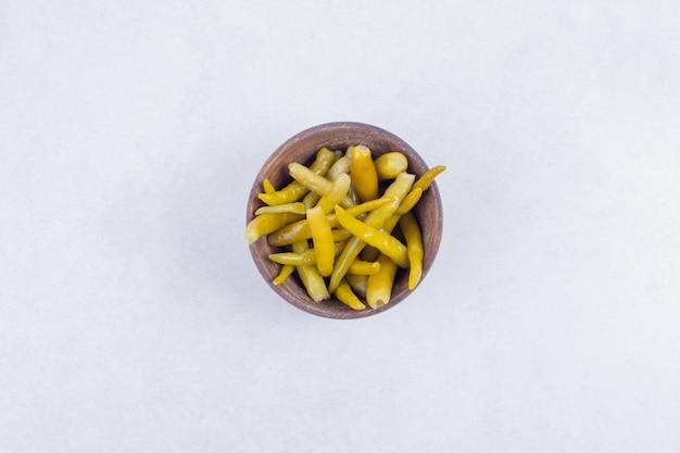 Маринованный острый перец в деревянной миске на белом фоне.