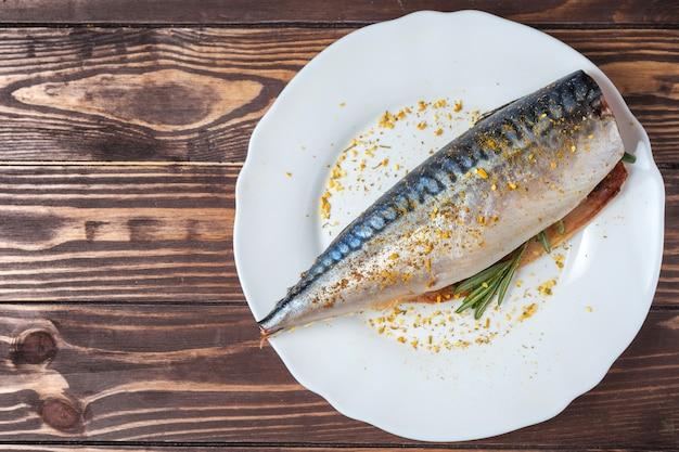 흰 접시에 절인 고등어. 준비되지 않은 날 생선. 전통 해산물 진미