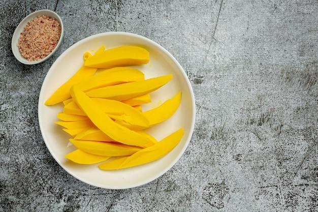 Pickled mango on dark wooden surface