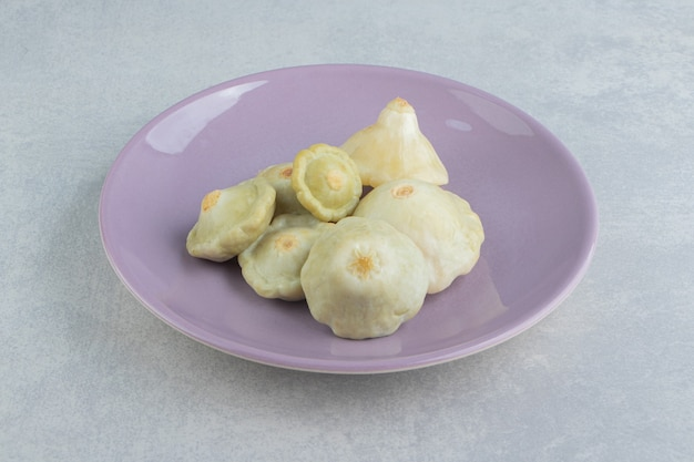 Mini zucchine sott'aceto in un piatto sulla superficie di marmo