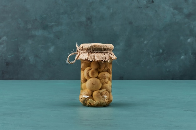 Pickled mushrooms in a glass jar on blue table.