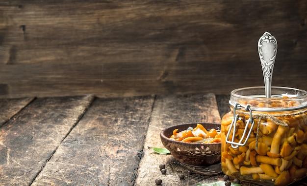 향신료와 허브와 함께 그릇에 절인 버섯. 나무 배경.