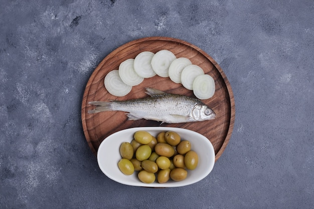 Pickled olives, fish and onion slices on wooden plate.