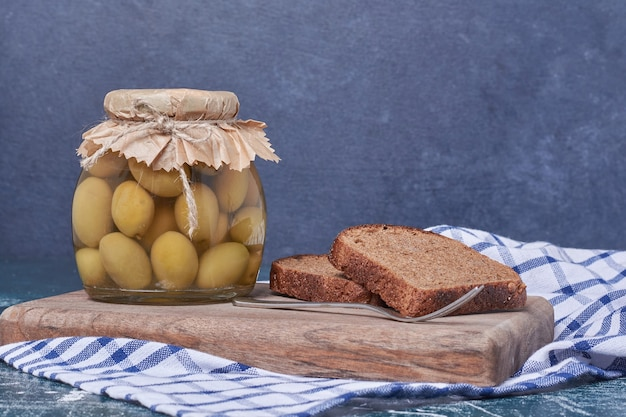 Pickled olives in glass jar with black bread slices on blue.