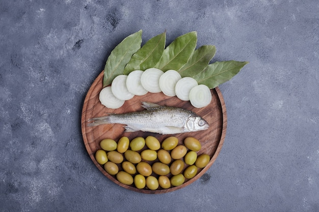 Pickled olives, leaves, fish and onion rings on wooden plate.