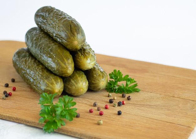 パセリとスパイスが白い背景で隔離の木の板に有機性キュウリのピクルスまたは発酵