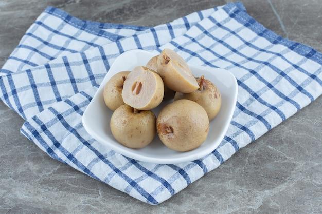 漬け物または浸したリンゴ、灰色の背景に缶詰のリンゴ。