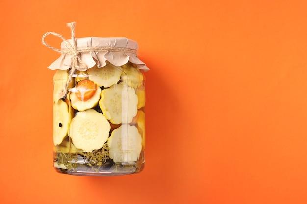 Маринованные патиссоны и огурцы в стеклянной банке на ярко-оранжевом фоне