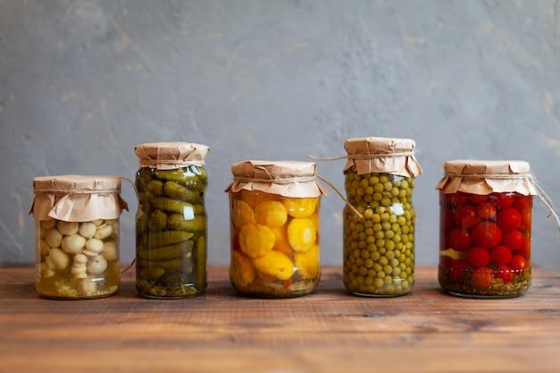 Маринованные патиссоны, огурцы, грибы, зеленый горошек и помидоры, консервированные в стеклянные банки
