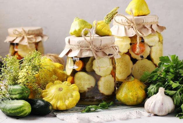 Маринованные патиссоны, огурцы с морковью и чесноком в стеклянных банках и свежие ингредиенты