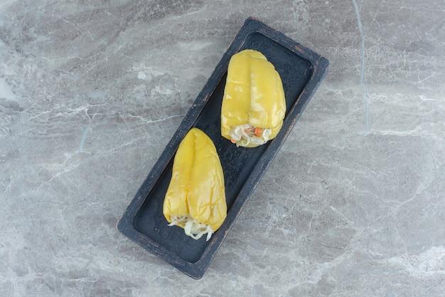 Peperoni sott'aceto ripieni di crauti su tavola di legno nera.