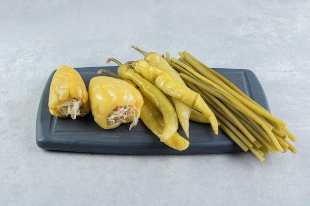 Peperoni sottaceto e verdure sul bordo scuro.