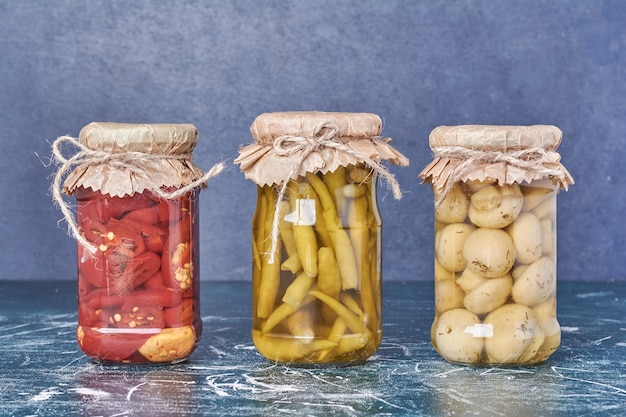 Pickled peppers and mushrooms in a glass jar on blue.