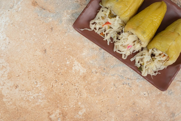 Маринованный перец, фаршированный квашеной капустой на коричневой тарелке.