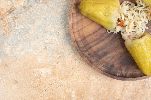 나무 접시에 소금에 절인 양배추를 채운 절인 고추