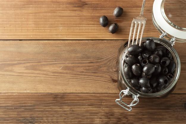 Pickled pitted black olives in glass jar, wooden background. mediteranian foods. copy space.