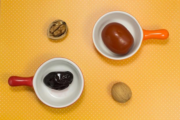 赤い皿に梅干し。オレンジプレートのトマトのピクルス。テーブルの上の2つのクルミ。上面図