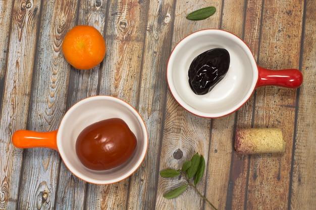 赤い皿に梅干し。オレンジプレートのトマトのピクルス。ワインのコルク。テーブルの上のマンダリンとグリーンの葉。上面図