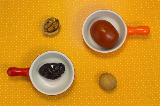 黄色の表面に梅とトマトのピクルス。クルミ。静物