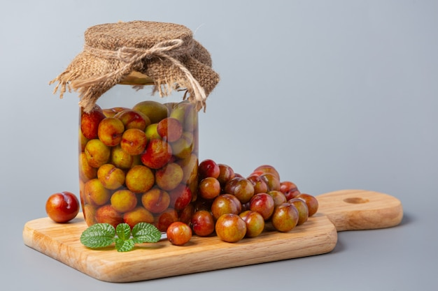 Pickled plums on gray surface.