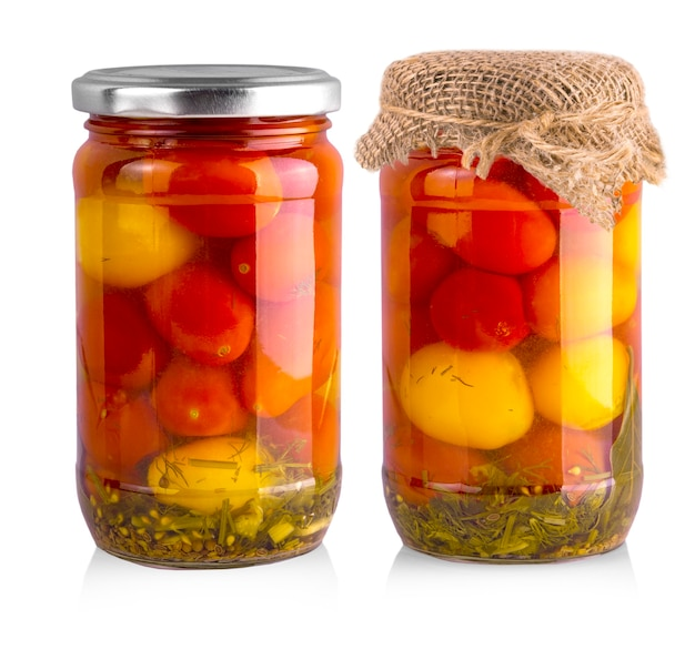 Маринованные красные и желтые помидоры в стекле, изолированные на белом.