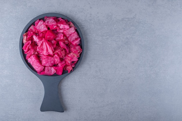 大理石の背景に、鍋に赤キャベツのピクルス。