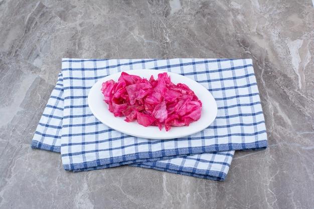 テーブルクロスと白い皿に赤キャベツのピクルス。