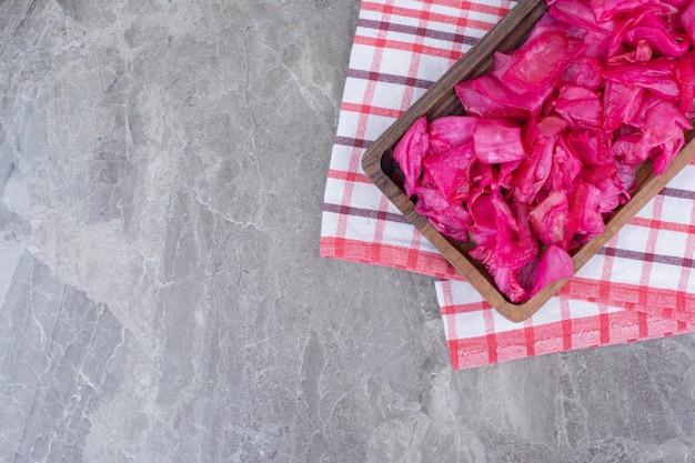 Маринованная красная капуста на деревянной тарелке.