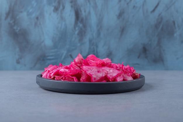 Cavolo rosso marinato in padella, sullo sfondo di marmo.