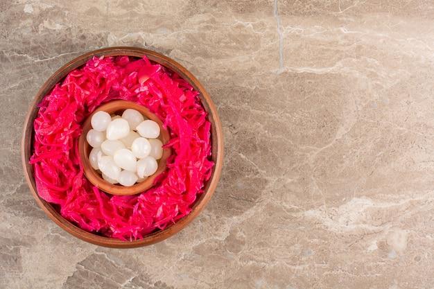 石のテーブルにニンニクのクローブを置いた赤キャベツのピクルス。