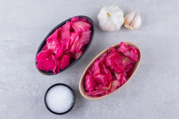 赤キャベツのピクルスと新鮮なニンニクとペッパーコーンを石のテーブルに置いたもの。